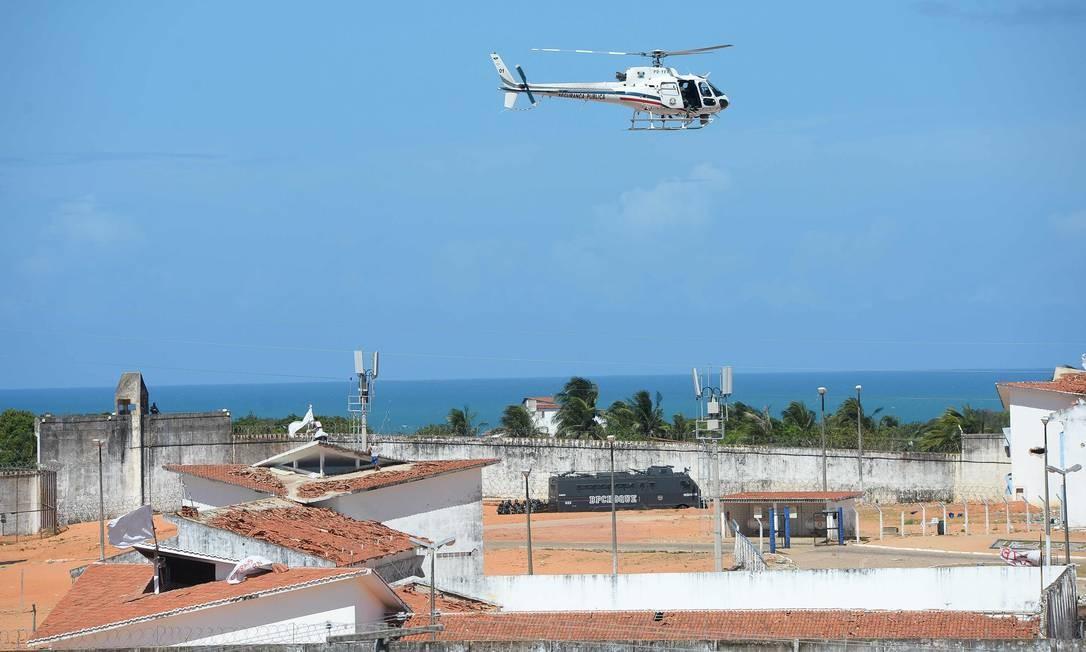 Um helicóptero da Polícia Militar sobrevoa a penitenciária para dar apoio à ação. Foto: ANDRESSA ANHOLETE / AFP