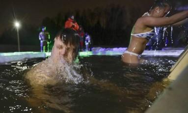 Russos mergulham em poço no vilarejo de Tyarlevo, nos arredores de São Petersburgo Foto: Dmitri Lovetsky / AP