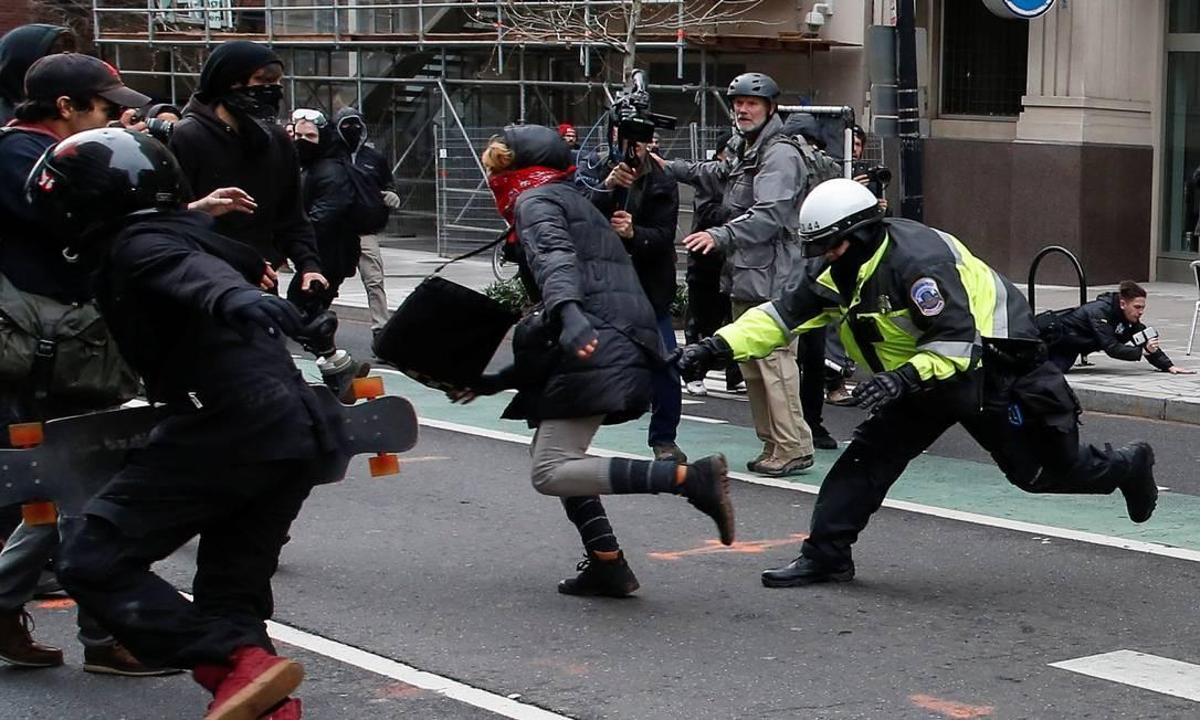 Policial de Washington tenta agarrar manifestante em local próximo a onde o novo presidente americano tomava posse Foto: ADREES LATIF / REUTERS