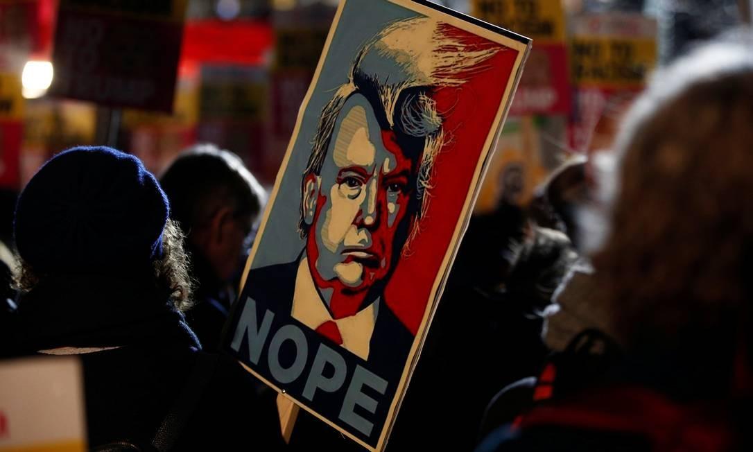 Manifestante segura cartaz na porta da embaixada dos EUA em Londres Foto: PETER NICHOLLS / REUTERS