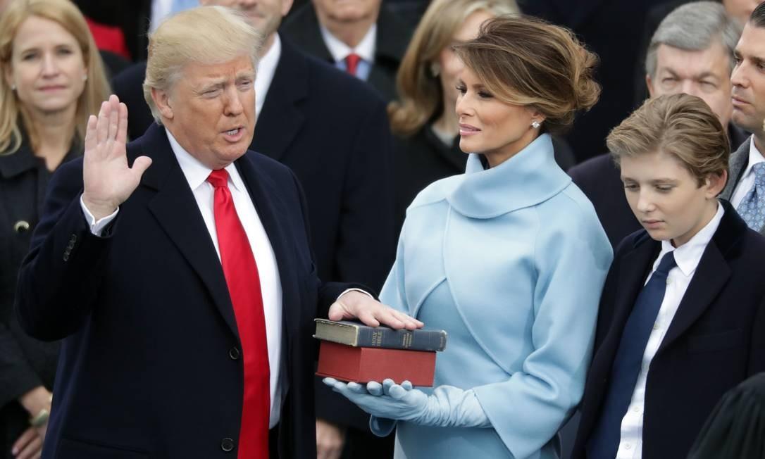 O presidente dos EUA, Donald Trump, durante o juramento ao lado da mulher Melania e seu filho Barron na cerimônia de posse no Capitólio, em Washington Foto: CHIP SOMODEVILLA / AFP