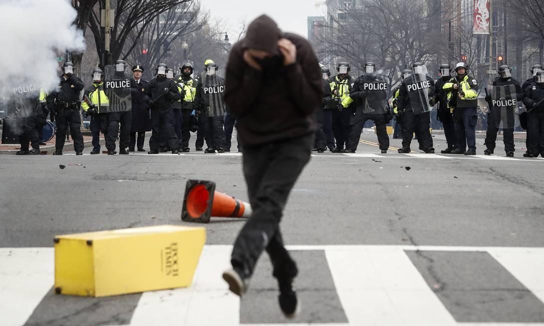 Manifestante corre de bomba de efeito moral lançada pela polícia em Washington Foto: John Minchillo / AP