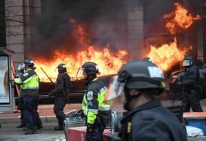 Policiais afastam manifestantes em meio a incêndio nas ruas de Washington Foto: BRYAN WOOLSTON / REUTERS