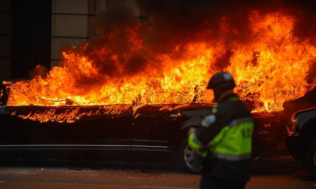 Policial observa uma limosine incendiada por manifestantes nas ruas de Washington Foto: BRYAN WOOLSTON / REUTERS