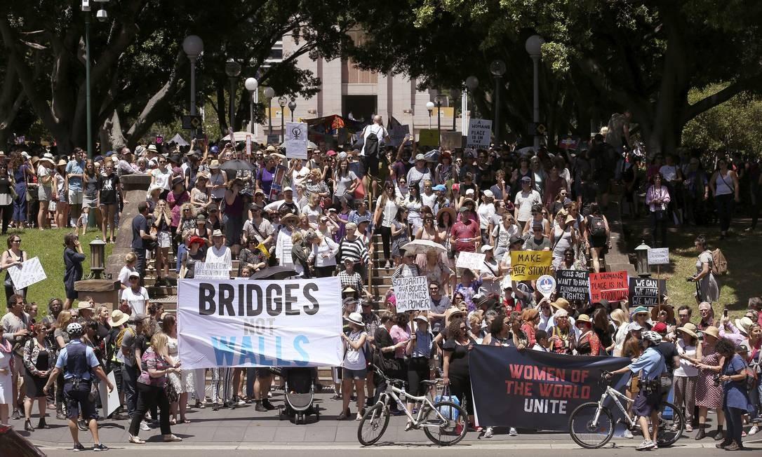 """Manifestantes da marcha de Sidney, na Austrália, seguram cartazes em que se leem """"Pontes, não muros"""" e """"Lute como uma mulher"""" Foto: Rick Rycroft / AP"""