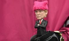 Manifestante segura boneco de Donald Trump com gorro rosa; o item virou símbolo da Marcha das Mulheres no sábado Foto: ROBYN BECK / AFP