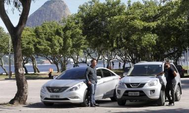 Os motoristas Homero (à esquerda) e Nazareno trabalham no Uber e no EasyGo, novo aplicativo lançado para os passageiros do Rio na semana passada Foto: Domingos Peixoto / Agência O Globo