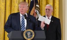 Trump segura a carta deixada por Barack Obama ao lado de seu vice, Mike Pence, em cerimônia na Casa Branca: críticas aos meios de comunicação e ironias no Twitter Foto: MANDEL NGAN / AFP