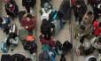 Passageiros fazem filas em estação de trem em Beijing Foto: NICOLAS ASFOURI / AFP