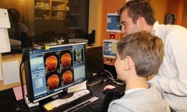 Ressonância. Uma das crianças que teve seu cérebro examinado observa as imagens ao lado de um dos pesquisadores Foto: Jesse gomez/divulgação