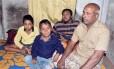 O comerciante Tofazzal Hossain com seus dois filhos e o neto, que sofrem de doença degenerativa Foto: STR / AFP