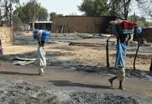 Crianças carregam seus pertences na fuga do grupo extremista Boko Haram em Maiduguri, na Nigéria Foto: AFP