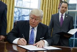 Donald Trump assina ordem executiva cancelando o Tratado Transpacífico, no Salão Oval Foto: Evan Vucci / AP