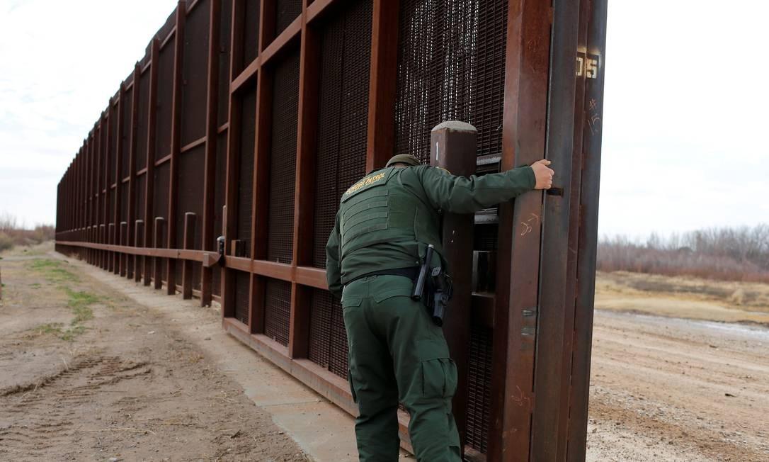 Um agente da fronteira americana abre uma das portas na cerca para a passagem de veículos, em El Paso, Texas Foto: TOMAS BRAVO / REUTERS