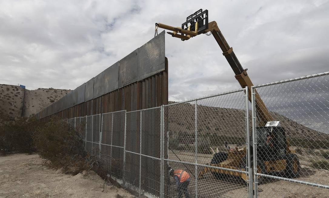 Trabalhadores levantam uma cerca maior entre as cidades de Anapra, México, e Sunland Park, Novo México; lá, há duas décadas, se celebra uma missa em homenagem aos mortos na tentativa de atravessar a fronteira Foto: Christian Torres / AP