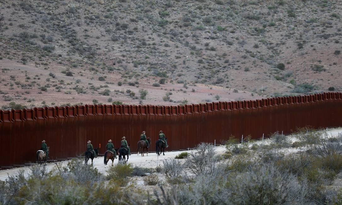 Agentes da patrulha de fronteira americana andam à cavalo pela divisa cerca na cidade de Jacumba, Califórnia Foto: MIKE BLAKE / REUTERS