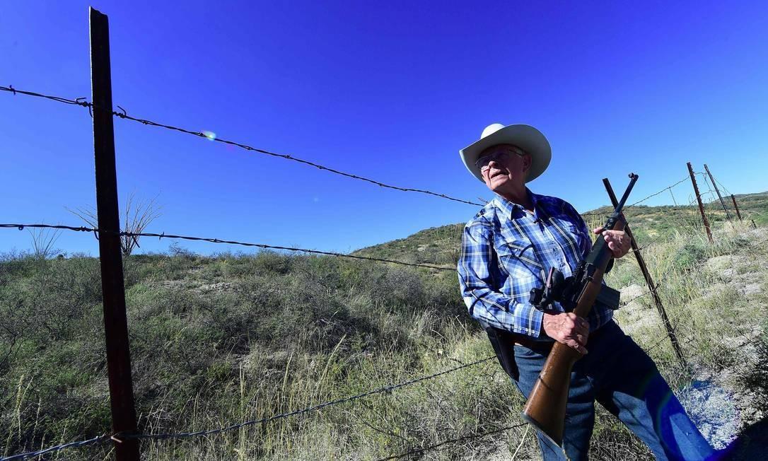 O vaqueiro Jim Chilton espera ao lado da cerca de fronteira entre México e EUA, na área em que passa por sua própriedade Foto: FREDERIC J. BROWN / AFP