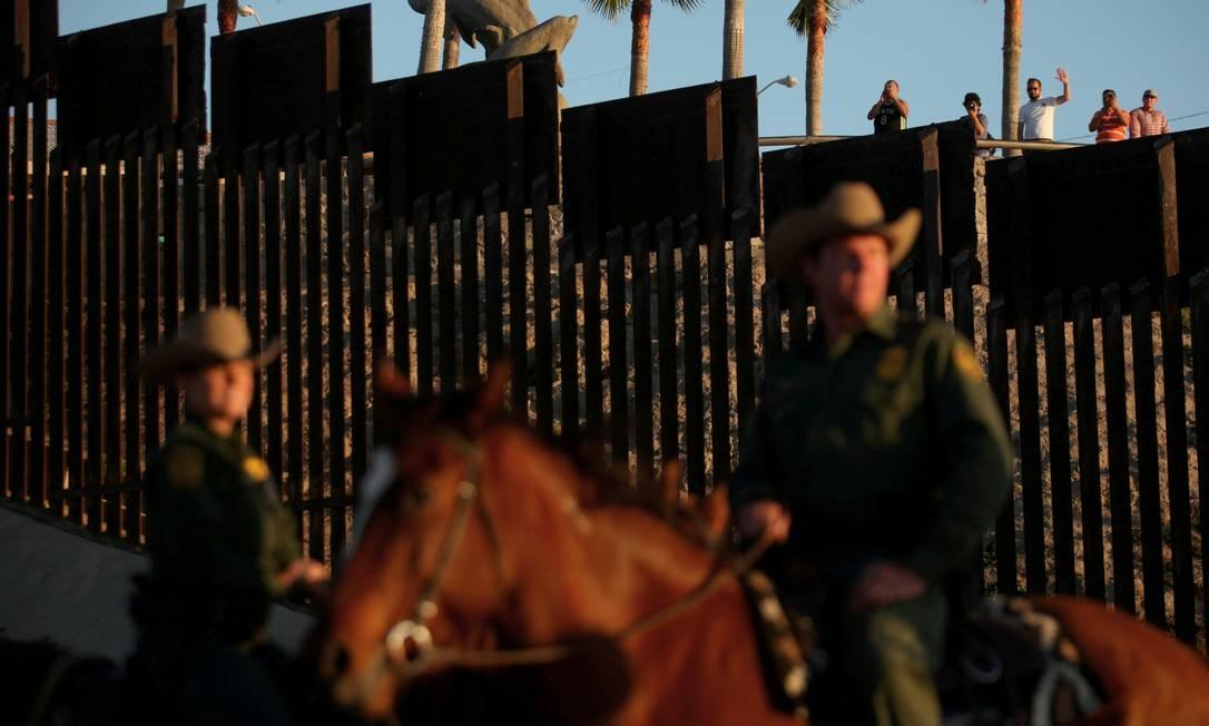 Mexicanos acenam para agentes da fronteira americana na divisa da cidade de San Diego, Califórnia Foto: MIKE BLAKE / REUTERS
