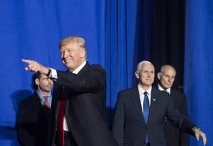 Acompanhado pelo vice Mike Pence e o secretário John Kelly (fundo, direita), Trump aponta para apoiadores Foto: NICHOLAS KAMM / AFP