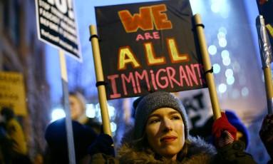Manifestante carrega cartaz com os dizeres 'Somos todos imigrantes' em protesto contra o plano de Donald Trump de construir um muro na fronteira com o México Foto: JOSHUA LOTT / AFP