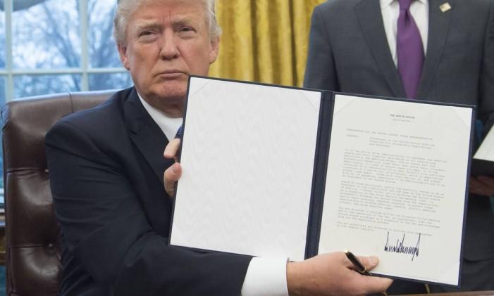 Donald Trump assina o decreto para saída da Parceria Transpacífica (TPP, na sigla em inglês) Foto: SAUL LOEB / AFP
