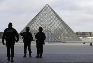 Polícia francesa patrulha o local perto da pirâmide do Louvre, em Paris Foto: CHRISTIAN HARTMANN / REUTERS