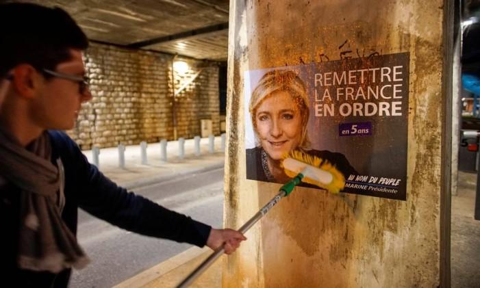 Jovens do partido Frente Nacional espalham cartazes da candidata Marine Le Pen, líder da extrema-direita francesa, em Lyon Foto: ROBERT PRATTA / REUTERS