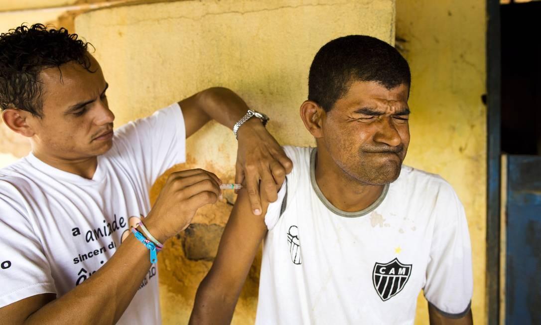 Agente de saúde de Imbé de Minas vacina morador de Córrego do Ouro, onde a febre amarela vem se espalhando Mônica Imbuzeiro / O GLOBO