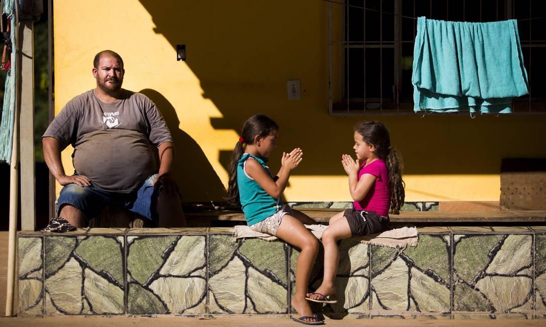 """Claudinei da Silva Campos, que também teve a doença, com duas sobrinhas: """"A dor na barriga era demais. Uma sensação horrível"""" Mônica Imbuzeiro / O GLOBO"""