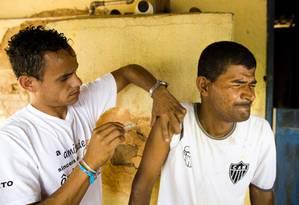 Em Minas, agentes de saúde aplicam a vacina em moradores Foto: Mônica Imbuzeiro / Agência O Globo