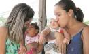 Caroline e a mãe, Lidiane, com Micaela e Maria Eduarda no colo: rotina de cuidados especiais com as pequenas, que têm microcefalia Foto: Paulo Nicolella