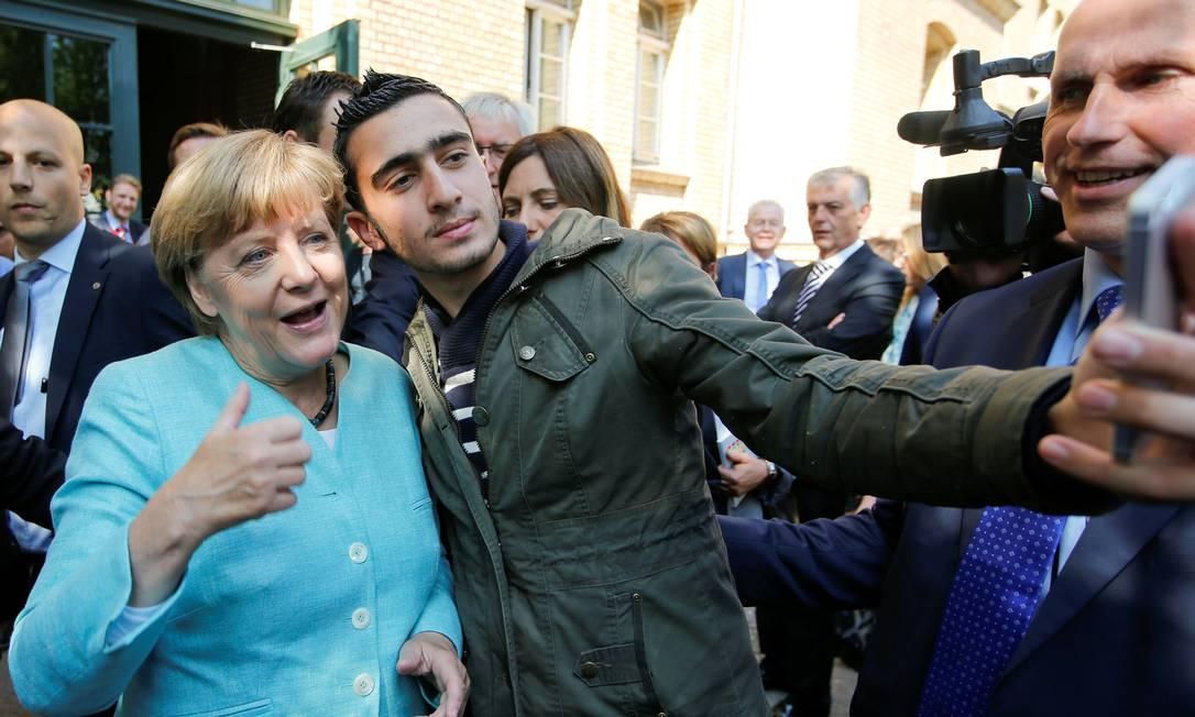 Anas Modaman tira selfie com Merkel em Berlim, em 2015: imagens do refugiado foram usadas para insinuar que ele era terrorista Foto: Fabrizio Bensch / REUTERS