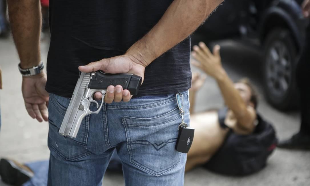 Um policial civil armado tenta impedir o ataque a uma loja de eletrônicos, em Vitória Foto: Diego Herculano / AP