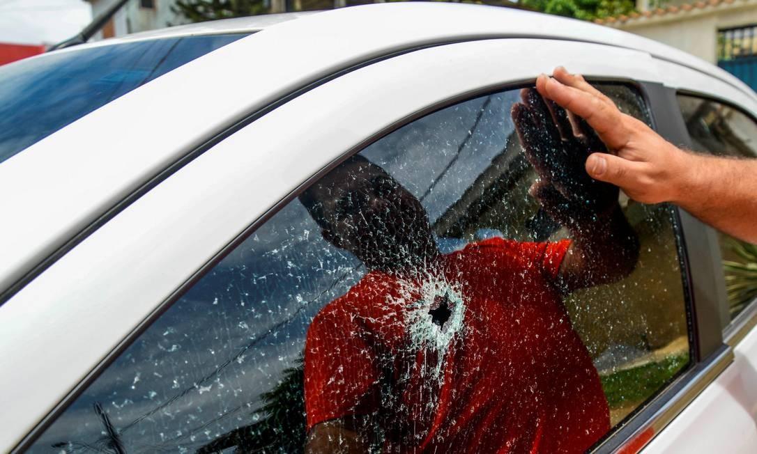 Um homem observa o vidro de seu carro, atingido por um disparo nas ruas de Vitória Foto: STRINGER / REUTERS