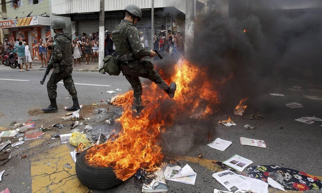 Soldado do exército tenta apagar fogo colocado em penus na porta do batalhão da PM Foto: Pablo Jacob / Agência O Globo