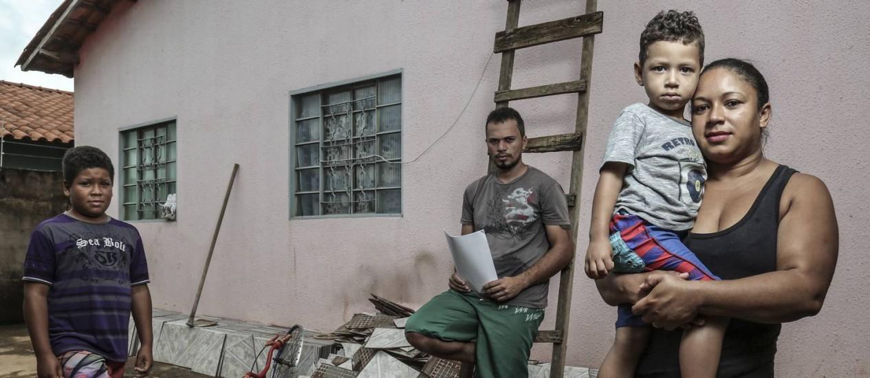 Wagner Amorim, ladeado pela mulher Rosimaria, com Enzo ao colo, e Marcelo Henrique: reingresso no Bolsa Família Foto: André Coelho / Agência O Globo