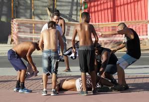 Torcedores do Botafogo tentam ajudar homem ferido após confusão no entorno do Engenhão Foto: Marcelo Theobald / Agência O Globo