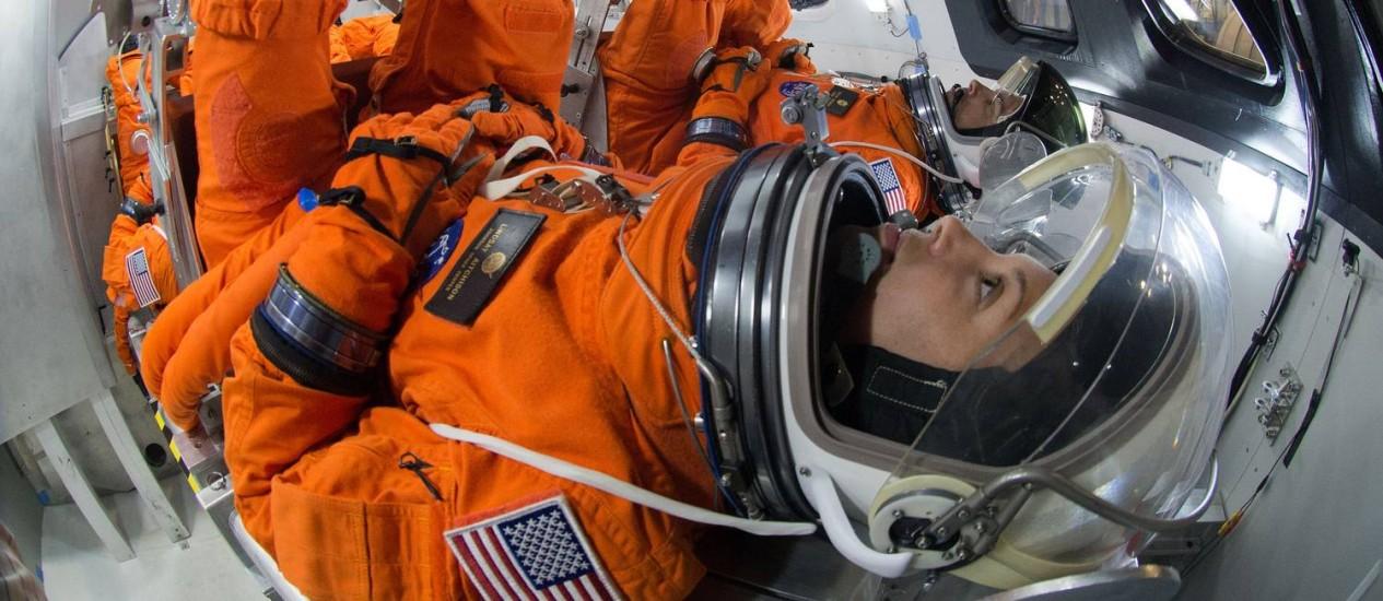 Astronautas em seus trajes dentro de uma cápsula espacial: em missões de longa duração, situações de emergência ou própria operação pode exigir que eles fiquem vestidos neles por longos períodos Foto: Nasa