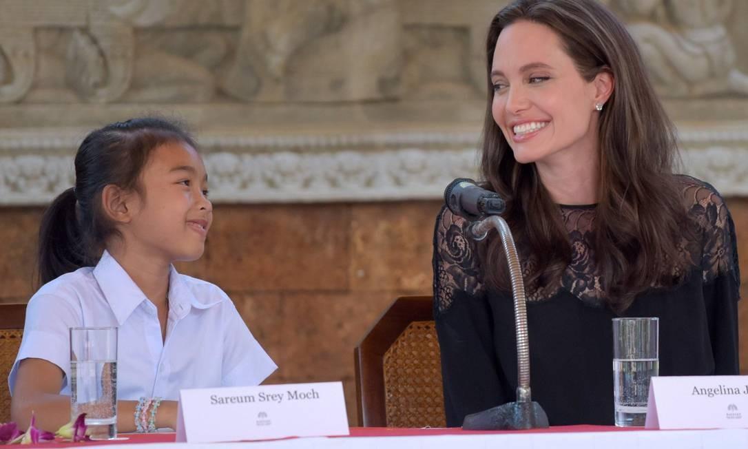 """Angelina posa ao lado da atriz do Camboja Sareum Srey Moch durante a entrevista coletiva. O filme é baseado no livro de memórias """"First They Killed My Father: A Daughter of Cambodia Remembers"""", da ativista Loung Ung Foto: TANG CHHIN SOTHY / AFP"""