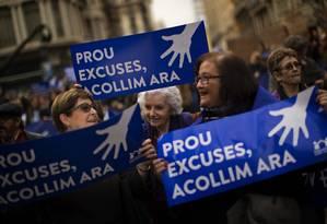 Manifestantes em Barcelona carregam cartazes exigindo a acolhida imediata de refugiados por parte do governo espanhol Foto: Emilio Morenatti / AP