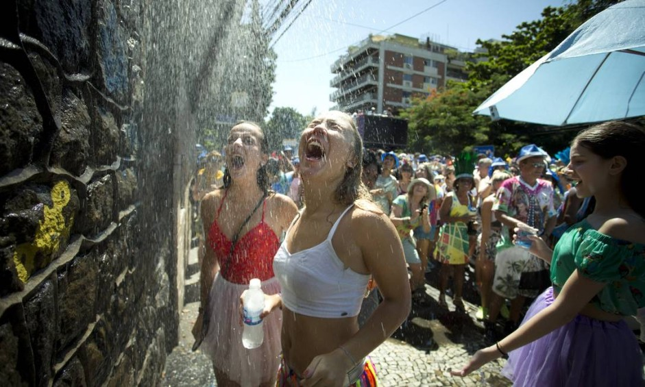 Pausa para refrescar o calorão: fiéis de uma igreja jogam água para refrescar foliões do Suvaco do Cristo Foto: Márcia Foletto / Agência O Globo
