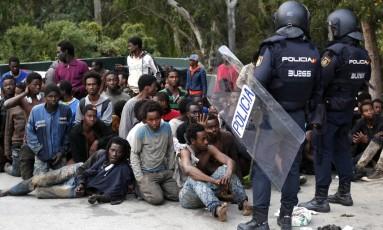 Migrantes que cruzaram fronteira de Ceuta são escoltados pela polícia Foto: Jesus Moron / AP