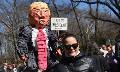 """Manifestante leva boneco que imita Donald Trump ao lado de placa que diz """"não é meu presidente"""" em Nova York Foto: TIMOTHY A. CLARY / AFP"""