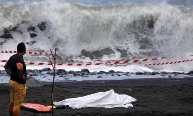 Policial trabalha ao lado de corpo de surfista na Ilha da Reunião Foto: RICHARD BOUHET / AFP