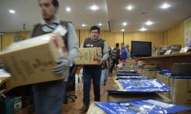 Membros do Conselho Nacional Eleitoral contabilizam votos em Quito Foto: RODRIGO BUENDIA / AFP