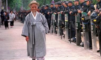 Homem sul-coreano vestindo roupa tradicional caminha em frente a uma barreira de policiais em Seul. País terá a população mais longeva do mundo em 2030, prevê estudo Foto: Ahn Young-joon / AP