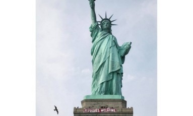 """In this photo provided by Vitória Londero, a giant banner saying """"Refugees Welcome"""" hangs on pedestal of the Statue of Liberty, Tuesday, Feb. 21, 2017, in New York. National Park Service spokesman Jerry Willis says the banner was hung from the public observation deck at the top of the statue's pedestal Tuesday afternoon. (Vitória Londero via AP) Foto: Vitória Londero / AP"""