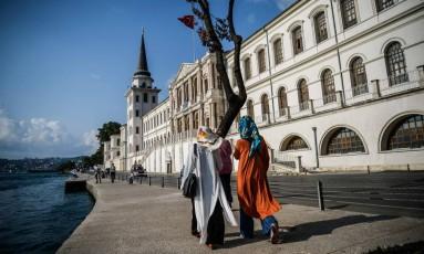 Duas mulheres usam hijab enquanto caminham em frente a escola militar Kuleli, nas margem do Estreito de Bosphorus, em Istambul Foto: Ozan Kose / AFP