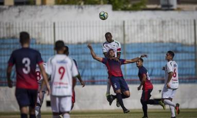 Douglas Assis, zagueiro da Cabofriense, disputa jogada aérea com o atacante João Carlos, do Bonsucesso Foto: Alexandre Cassiano / Agência O Globo