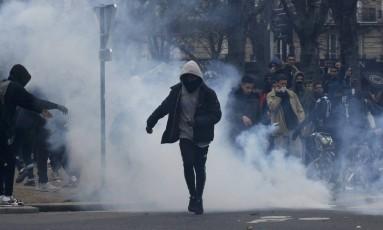 Manifestante foge de gás lacrimogênio durante protesto em Paris, na França. A polícia, no entanto, disse que não houve confronto na manifestação Foto: GONZALO FUENTES / REUTERS